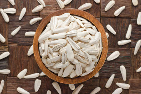 white sunflower seeds in bowl on wooden table background.