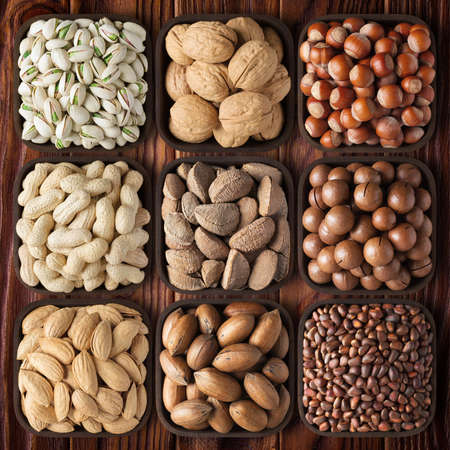 assorted nuts on wooden table background. mix raw food as snack. 版權商用圖片