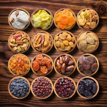 assorted dried fruits and berries in wooden bowls, top view. organic food background 版權商用圖片