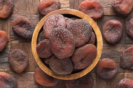 chocolate dried apricots in bowl on wooden table background.