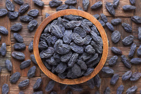 blue raisins, dried grapes in bowl on wooden table background. 版權商用圖片