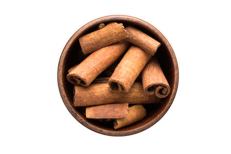 cinnamon sticks seasoning in a wooden bowl, top view. spice isolated on white