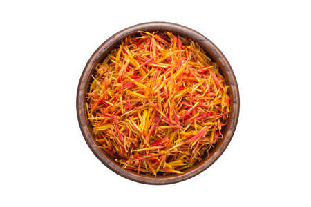Dried saffron seasoning in a wooden bowl, top view. spice isolated on white
