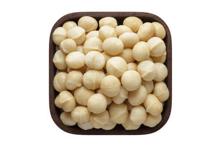 macadamia nuts peeled in wooden bowl closeup. vegetarian food isolated on white.