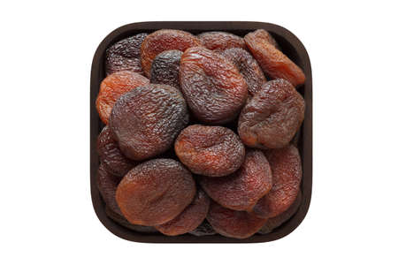 chocolate dried apricots in wooden bowl closeup. vegetarian food isolated on white.