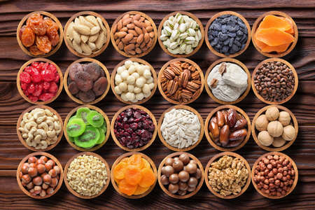 mix nuts and dried fruits on table background. raw food in wooden bowls, top view.