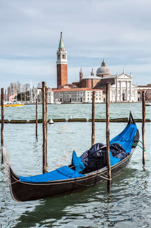 saint mark square: Gondola moored by Saint Mark square with church in the background - Venice, Italy, Europe Stock Photo