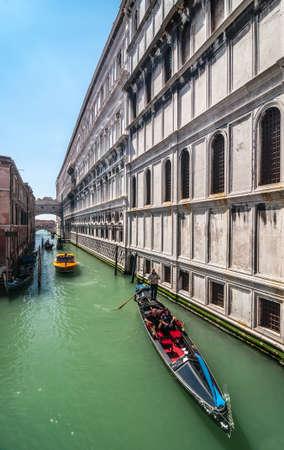 VENICE, ITALY - APRIL 13: Gondolier with tourists in gondola on canal Rio di Palazzo near Palazzo Ducato and Bridge of Sighs, Venice, Italy, April 13, 2013