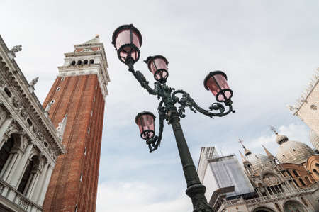 Beautiful ornate lampposts in Piazza San Marco against campanile San Marco in Venice, Italy.