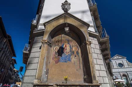 balcony view: Icon at the corner of building and behind the Basilica of Santa Maria Novella, Florence, Toscany, Italy.