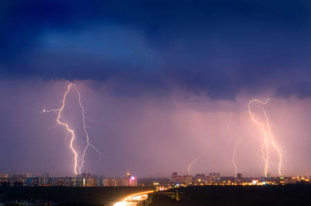 Lightning strike over city in purple light. Stock Photo