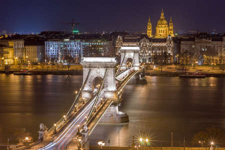 Night View of the Szechenyi Chain Bridge over Danube River and church St. Stephens Basilica in Budapest, Hungary. View from Royal Palace in Buda Castle.
