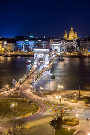 Night view of the Szechenyi Chain Bridge over Danube River and church St. Stephens Basilica in Budapest, Hungary. View from Royal Palace in Buda Castle. Stock Photo