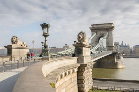 The Szechenyi Chain Bridge is a suspension bridge that spans the River Danube between Buda and Pest. The Guardian lions at each of the abutments carved in stone. Stock Photo