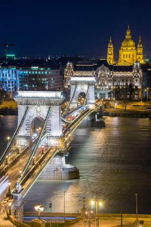 stephen: Night view of the Szechenyi Chain Bridge over Danube River and church St. Stephens Basilica in Budapest, Hungary. View from Royal Palace in Buda Castle. Editorial