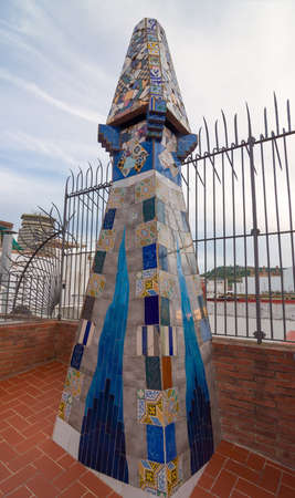 Barcelona, Spain - September 20, 2014: Design of the roof of Palace Guell - Palau Guell - Gaudi Chimney: broken tile mosaics and strange decorated chimneys are evident in his early work.