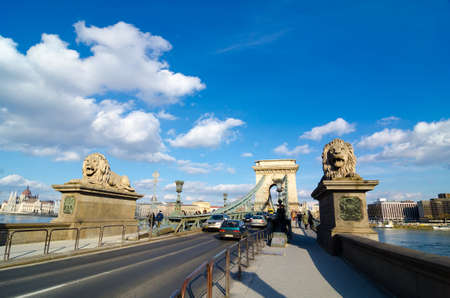 szechenyi: BUDAPEST, HUNGARY - FEBRUARY 20, 2016: The Szechenyi Chain Bridge is a suspension bridge that spans the River Danube between Buda and Pest. The Guardian lions at each of the abutments carved in stone.