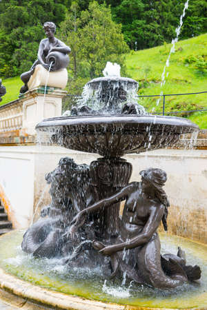 Ettal, Germany - June 5, 2016: Fountain in Linderhof Palace garden. The Castle built by King Ludwig II of Bavaria in 19th century.