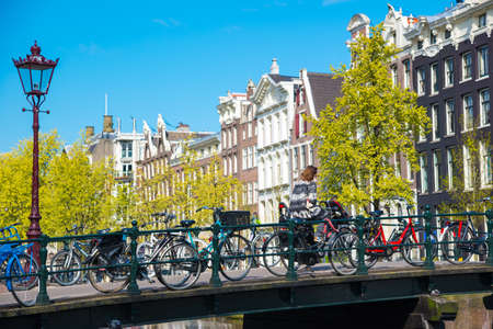 Amsterdam, Netherlands - April 19, 2017: Amsterdam canal scene with bicycles and bridges