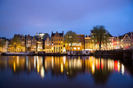 them: Amsterdam, Netherlands - April 21, 2017: View of the Amsterdam canals and embankments along them at night.