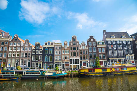 Amsterdam canals with boats and typical Dutch houses, Netherlands.