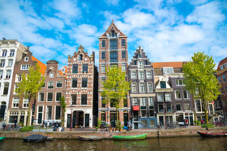 City view of Amsterdam, typical dutch houses and boats, Holland, Netherlands.
