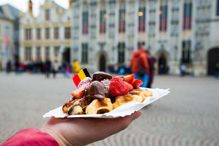 Belgium waffle with chocolate sauce and strawberries, Bruges city background, Belgium.