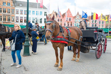 Bruges, Belgium - April 17, 2017: Horse carriage on Grote Markt square in Belgian city of Bruges. Editorial