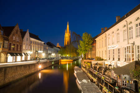 Bruges, Belgium - April 18, 2017: Dijver Canal and the Our Lady Church of Bruges, Belgium.