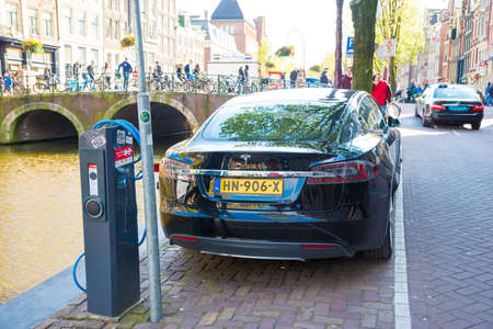 Amsterdam, Netherlands - April 19, 2017: A Tesla Model S electric car charging at a charging station on the street by a canal in Amsterdam. Editorial