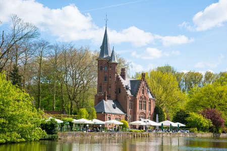 Bruges, Belgium - April 17, 2017: Minnewater castle at the Lake of Love in Bruges, Belgium