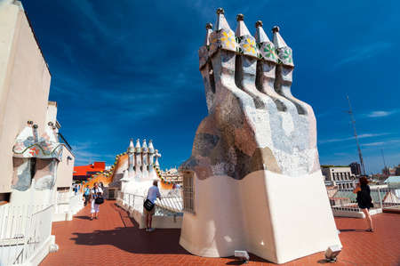 Barcelona, Spain - September 19, 2014: Rooftop of the house Casa Batllo - House of Bones designed by Antoni Gaudi. Ceramic tiles, with tower and bulb. Dragon's spine roof arch. Barcelona, Spain.