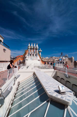 Barcelona, Spain - September 19, 2014: Rooftop of the house Casa Batllo designed by Antoni Gaudi. Ceramic tiles, with tower and bulb. Dragon's spine roof arch. Barcelona, Spain. Editorial