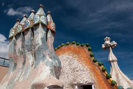 Barcelona, Spain - September 19, 2014: Rooftop of the house Casa Batllo designed by Antoni Gaudi. Ceramic tiles, with tower and bulb. Dragon's spine roof arch. Barcelona, Spain.