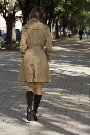 Young woman in coat walking along the avenue Stock Photo - 3585799