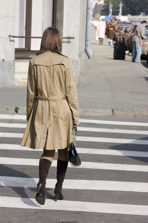 Young woman walks zebra crossing