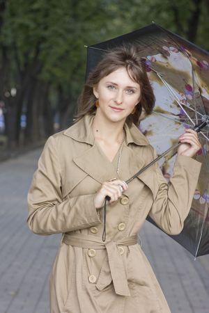 Yong woman with umbrella walking along the avenue Stock Photo - 3640917