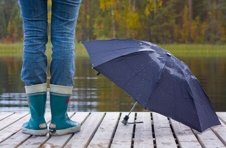 Legs booted gum boots and umbrella in front of the yellow trees