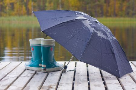 Fall, black umbrella and blue gum boots against a background of yellow trees