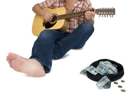 musician playing guitar with a hat full of money in front of him Stock Photo