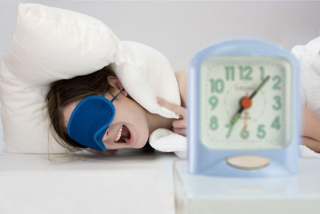 young woman closing her ears with pollow not to hear alarm clock