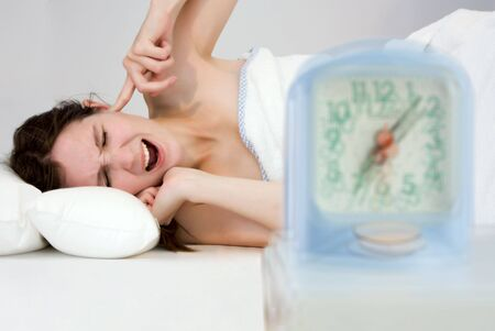 young woman closing her ears not to hear alarm clock