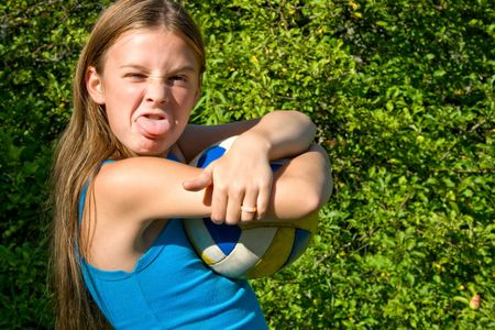 little girl with ball puting out her tongue Stock Photo