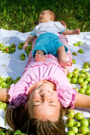 little girl and her baby brother lying among apples Stock Photo