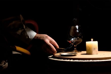 an arm with smoking cigar and glass of cognac