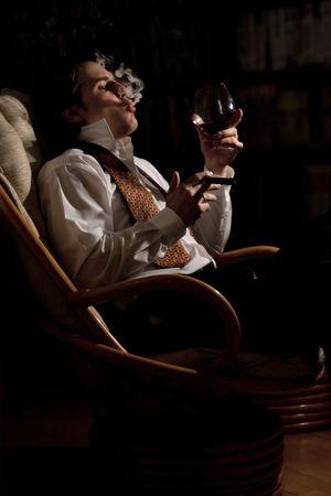 young man smoking cigar and drinking congac at night
