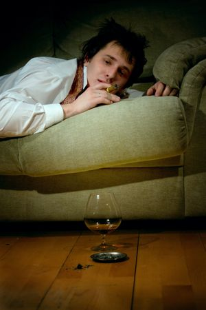 young man smoking cigar and drinking congac at night