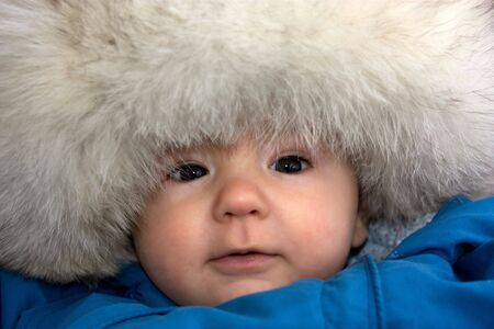 baby in big fur-cap outdoors