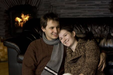 young beautiful couple near the fireplace photo