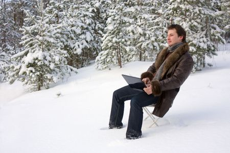 young man with laptop outdoors photo